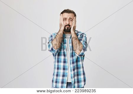 Studio shot of european bearded man squeezing face with hands, expressing regret and sadness. Employer just made huge mistake he feels sorry about. Person broke TV by hitting it with ball.