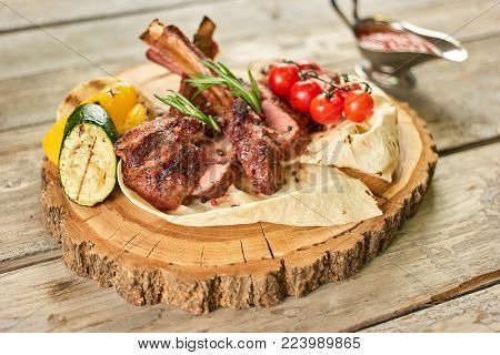 Roasted racks of beef with vegetables. Prepared roasted racks of beef with vegetables on lavash on wooden plate.