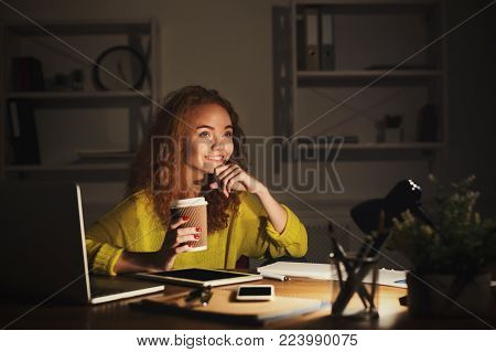 Happy female freelancer at home office workplace at night. Smiling woman drinking take away coffee, doing paperwork, using gadgets. Working hard, success, small business and technology concept