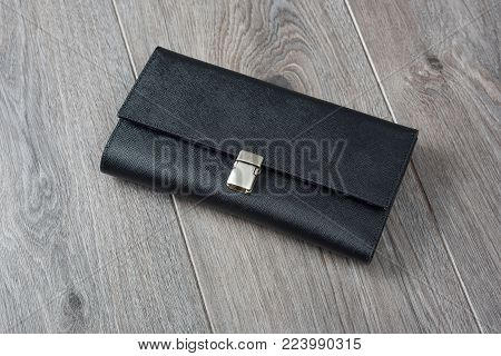 Stylish black wallet made from black colored leather with a silver metallic backstop. It lays on a brown wooden surface.