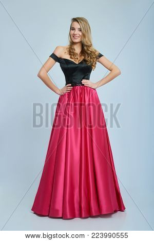 Wonderful girl wearing amazing long pink and black evening dress. Good choice for prom. Girl is very beatiful and has blonde curly hair, nice light make-up. She has pretty smile. Photo was taken on white studio background.