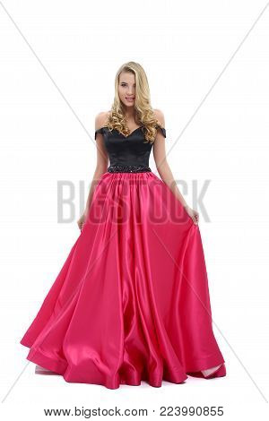 Wonderful girl wearing amazing long pink and black evening dress. Good choice for prom. Girl is very beatiful and has blonde curly hair, nice light make-up. Photo was taken on white studio background.