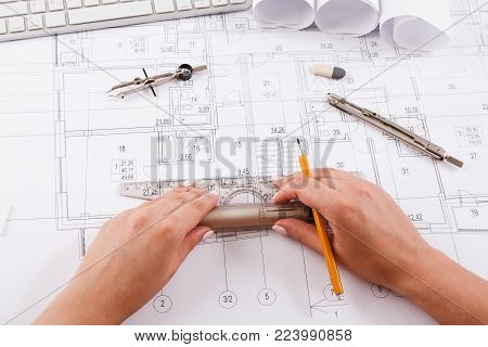 Architect drawing architectural project. Unrecognizable designer hands working with building blueprint, copy space
