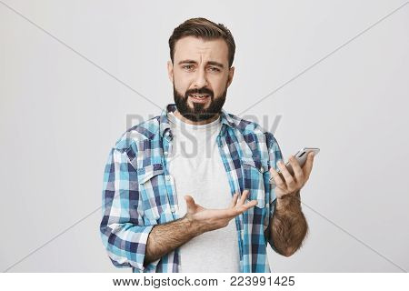 Indoor shot of caucasian guy with beard and moustache in checked shirt, holding phone and gesticulating, expressing complaint and frustration, over gray background. Personal assistant insulted him.