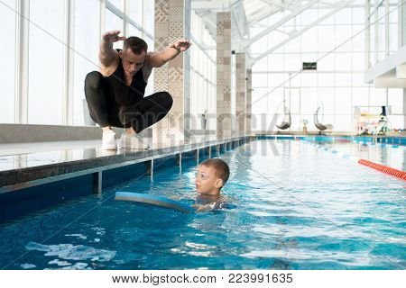 Working process in spacious swimming pool: little boy in goggles using kickboard, his middle-aged coach sitting on haunches and giving him necessary instructions while teaching him to swim
