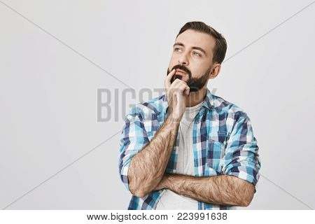 Idea and thought concept. Curious man with beard and stylish haircut standing over gray background in thoughtful pose and half-turned face, looking aside. Guy thinks what he should order.