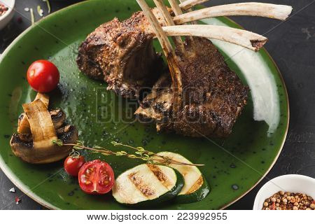 Rack of Lamb with grilled vegetables. Restaurant serving of bbq meat with mushroom, zucchini and cherry tomato, closeup