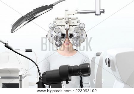 optometrist exam, eyesight  woman patient with phoropter in optician office