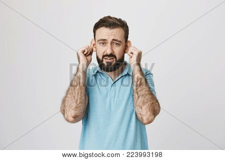 Adult bearded man with gloomy smile stretching ears, imitating sad monkey, over gray background. Guy is tired of hearing lies from his close friends. Fed up of listening demands.