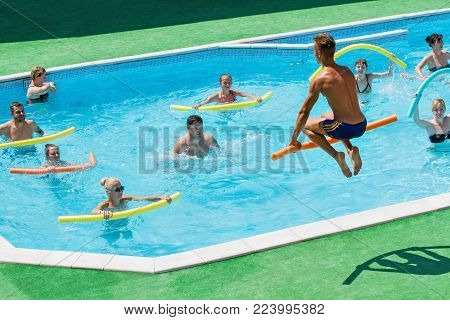 Fitness group doing aerobical excercises in swimming pool at aqua park. Sport and leisure activities. Trainer in the jump. Aquapark AQUADROM, UKRAINE, Dnepr - JULY 26, 2015.