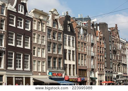AMSTERDAM, NETHERLANDS - APRIL 20, 2017: Typical gabled houses on Damrak street in Amsterdam, Holland, Netherlands