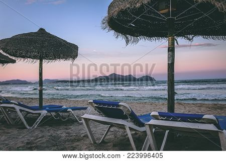 Beach beds and straw umbrellas at Playa de Muro Beach, Alcudia, Mallorca, Spain, beautiful six kilometres long Blue Flag, white sandy beach in the north of Mallorca.