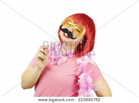 Portrait of a young chubby girl in a red wig with a carnival mustache on her face
