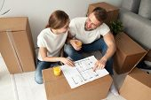 Happy couple discussing house plan looking at blueprint planning new home interior design, happy homeowners share furnishing remodeling ideas sitting on floor with moving boxes drinking orange juice poster