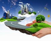 human hand holding a city on green grass hill poster
