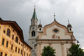 Tower and parish church Santi Filippo e Giacomo Apostoli at main square in Cortina d'Ampezzo, Italy poster