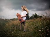 The girl with plush bear. Stormy sky, tall grass fields. The concept of children's loneliness, the character of the child poster