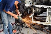 Electric wheel grinding on chassis of a car - auto body repair shop poster