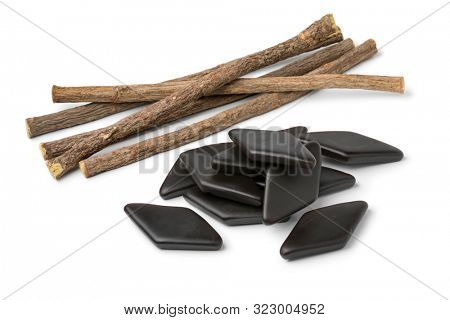 Heap of dried Licorice roots and black salt licorice confectionary, a Dutch treat, isolated on white background
