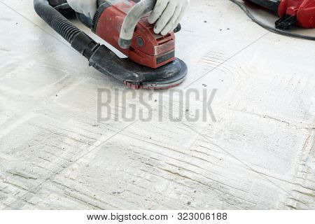 Construction Worker Uses A Concrete Grinder For Removing Tile Glue And Resin During Renovation Work