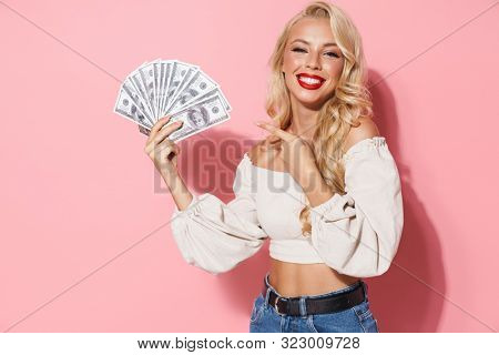 Image closeup of gorgeous seductive woman wearing red lipstick smiling while holding cash money isolated over pink background