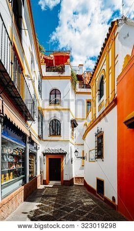 Old Picturesque Passageway In The Medieval Jewish Quarter Of Santa Cruz In Seville, Andalusia, Spain