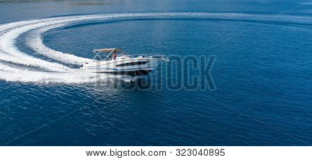 Aerial view of speed motor boat on open sea, creating wheel shape. Travel and leasure activities concept