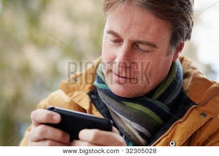 Man Texting On Smartphone Wearing Winter Clothes poster