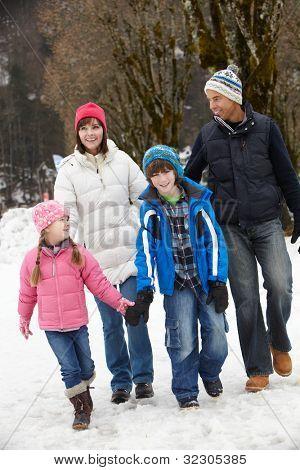 Family Walking Along Snowy Street In Ski Resort
