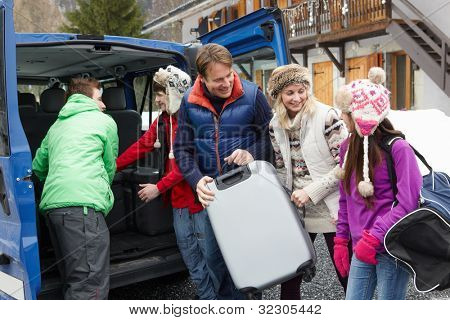 Family Unloading Luggage From Transfer Van Outside Chalet On Ski Holiday
