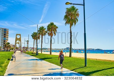 San Antonio De Calonge, Spain - August 21, 2018. Tourists Crossing The Seafront Promenade Of Sant An