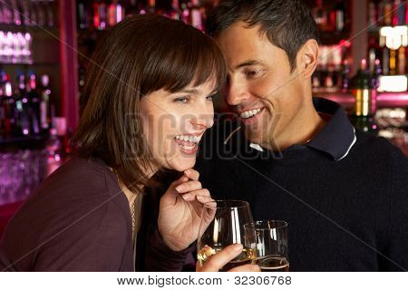 Couple Enjoying Drink Together In Bar