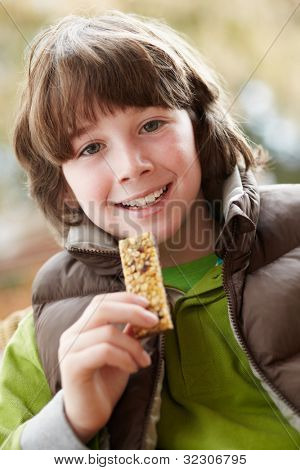 Boy Eating Healthy Snack Bar Wearing Winter Clothes