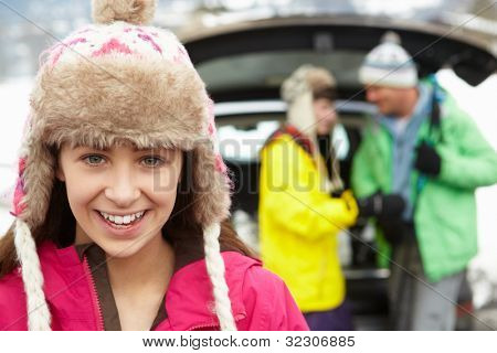 Teenage Girl Smiling At Camera Whilst Family Load Skis In Boot Of Car
