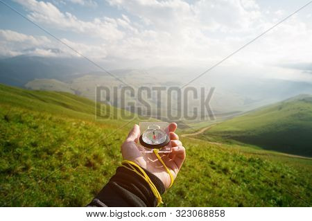 Male Hand With A Magnetic Compass Ea Against The Backdrop Of A Beautiful Landscape At Sunset. The Co