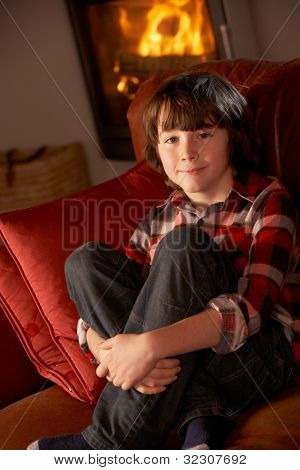 Young Boy Sitting On Sofa By Cosy Log Fire