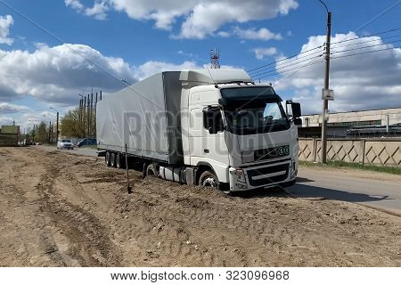 A Truck Stuck In The Sand On The Side Of The Road.