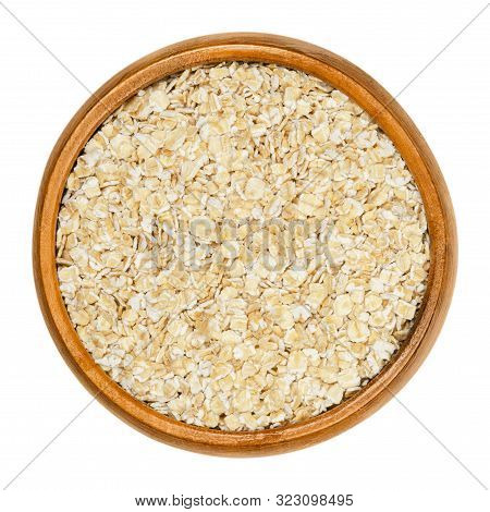Small-leaved Oatmeal, Rolled White Oats In Wooden Bowl. Dehusked Hulled Oats, Rolled Into Flakes, Fo