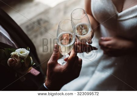 Close Up Of Married Couple Toasting Champagne Glasses At Wedding Party. Hands Bride And Groom Clinki