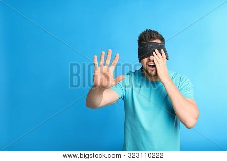 Man With Black Blindfold On Blue Background, Space For Text