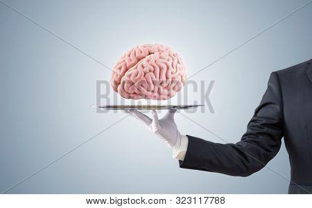 Businessman offering human brain on silver tray