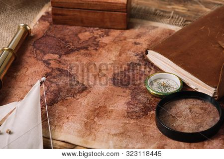 Old World Map Near Telescope, Leather Notebook And Compass On Hessian