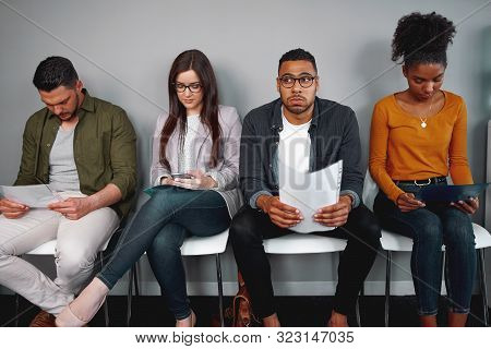 Worried And Stressed Man Holding His Resume Sitting With Other Candidates Waiting For The Job Interv