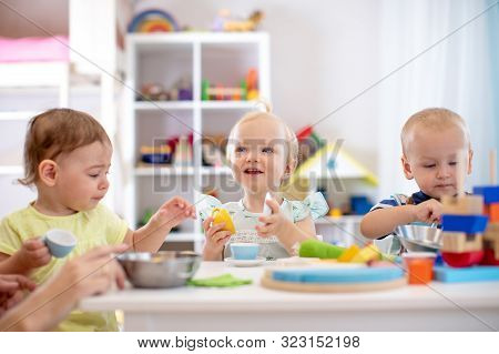 Babies Playing Together In Kindergarten Or Creche. Kids Sitting At Table In Nursery Or Daycare