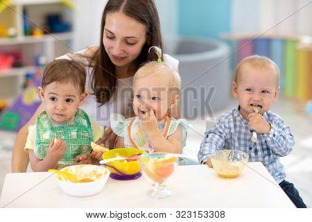 Babies Having Lunch In Kindergarten. Kids Eat Healthy Food In Creche. Carer With Little Children Sit