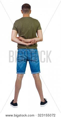 Back view of young manin shorts looking. Rear view people collection. backside view of person. Isolated over white background. A guy in shorts is standing and hands clasped behind his back.
