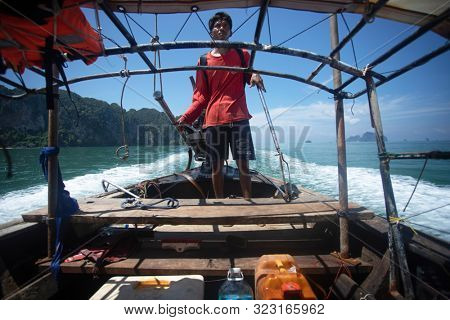 Krabi, Thailand - July 27, 2019: Local Thai man drive longtail boat, transporting tourists from one island to another, Krabi, Thailand.