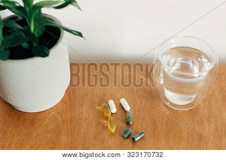 Dietary Supplements. Omega 3, Spirulina, Chlorophyll,magnesium  Capsules And Glass Of Water On Woode