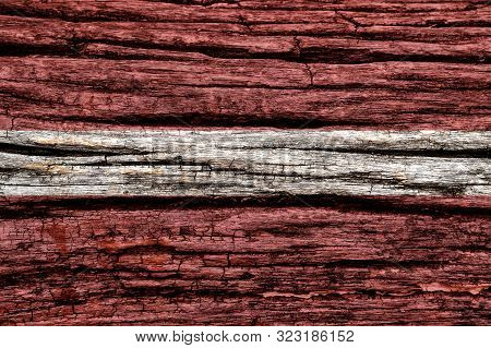 Latvia Flag On Old Decrepit Wooden Surface. Textured Background For Creativity And Design.