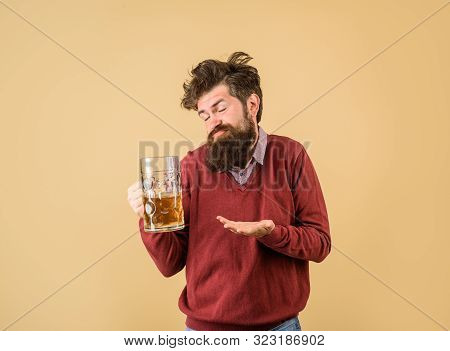 Oktoberfest. Alcohol. Drunk man with glass of craft beer. Man drinking draught beer at bar or pub. Bearded man holds glass with delicious ale. Man tasting draft beer. Bearded hipster drinking beer poster